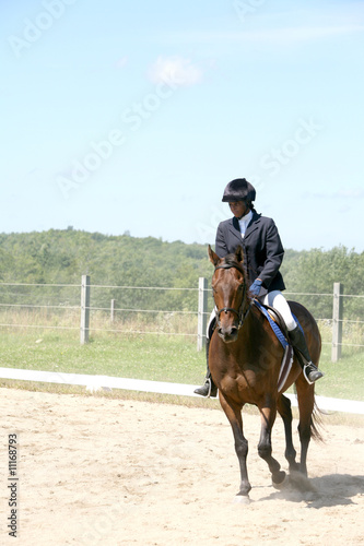 black teenage girl riding her horse in the show ring