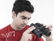 asian male of indian origin looking through the binocular