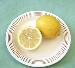 whole and half lemon on plate