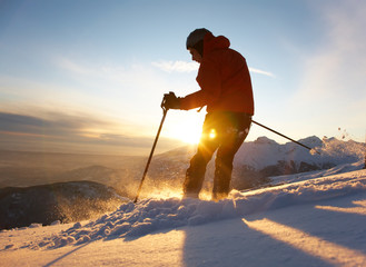 Freerider skier moving down in snow powder at sunset