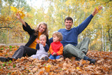 family of four sits in autumn park. parent hands up. poster