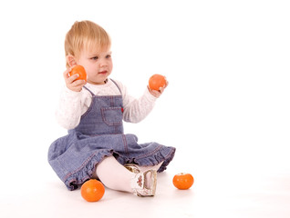 Little girl holding mandarines