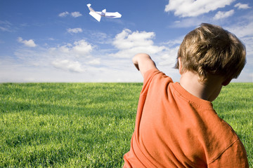 young boy flying a paper plane