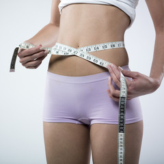 woman's belly and tape measure