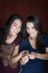 Two young women listening to music