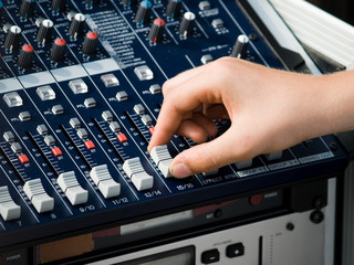 Human Hand using an audio mixer to tune the volume