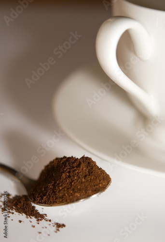 Spoon with coffee and white coffee cup