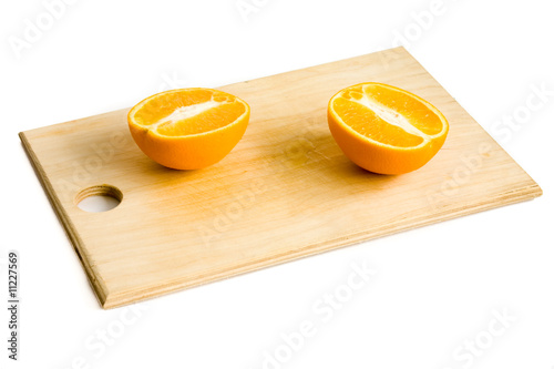 still life of two orange halves on wooden plate