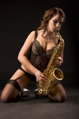 Retro woman saxophonist in lingerie on her knees