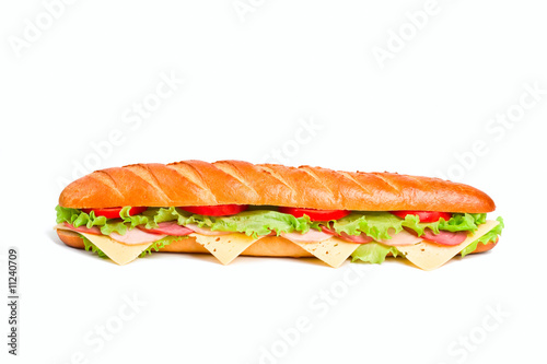 long sandwich with lettuce, tomatoes, ham, turkey and cheese