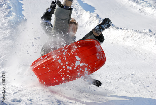 Boy in the Air with His Sled While Sledding Down the Hill