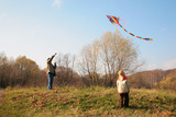 Grandfather and the grandson start a kite poster