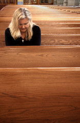 Woman praying in church pew