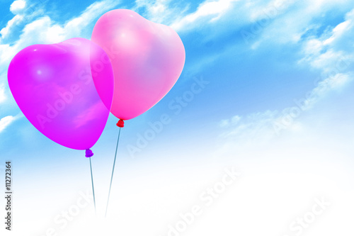 Colored balloons in a heart shape on blue sky