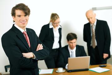 Business Team bei der Arbeit – Mann steht vorn