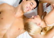 Portrait of young happy amorous couple in bedroom