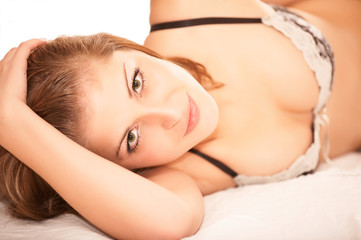 Young beautiful woman lies on bed with smile, isolated