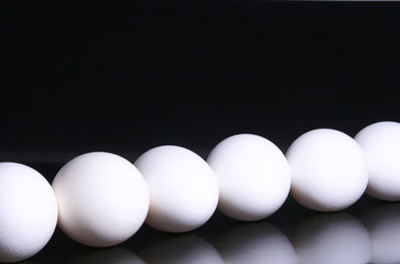 Eggs lined up on black reflective