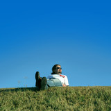 Young man is relaxing on the grass poster