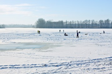 Ice-skating on frozen lake behind sunny of the day ..
