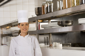 Female chef posing in commercial kitchen