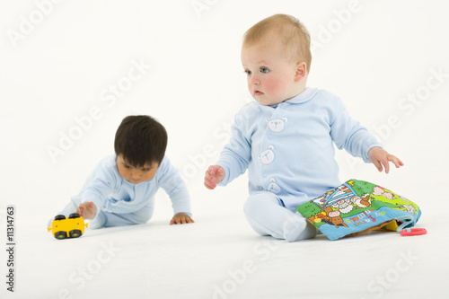 Two baby boys playing with toys