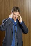 Businessman experiencing a headache rubbing his temples poster