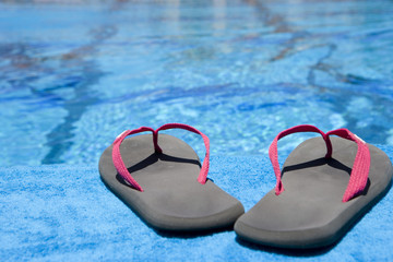Close up of flip flops next to swimming pool