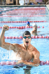Young man cheering after winning swimming competition