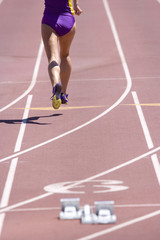 Female athlete running on race track