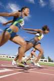 Female athletes clearing finish line on race track