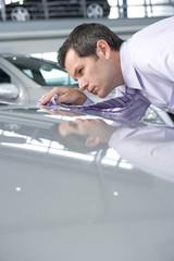 Salesman shining car with tie