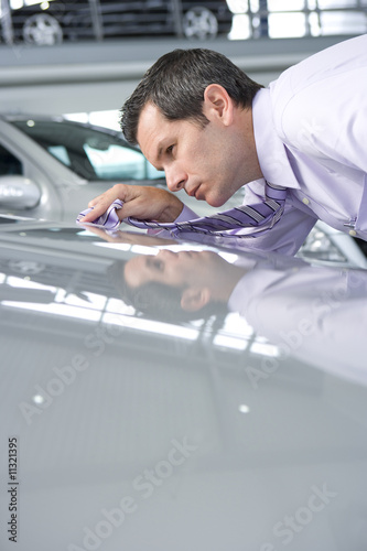Salesman shining car with tie