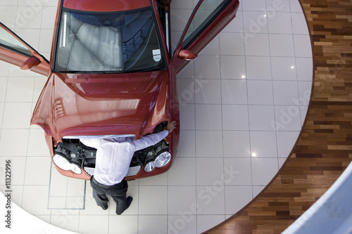 Man inspecting engine of new car