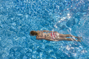 Teenage girl swimming in swimming pool