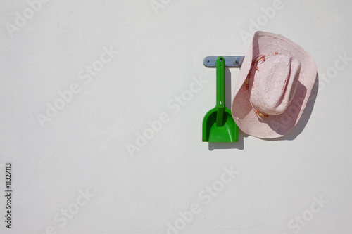 Cowboy hat and plastic shovel hanging on wall hook