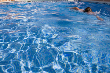 Woman swimming laps in swimming pool