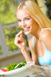 Portrait of young happy smiling woman eating salad