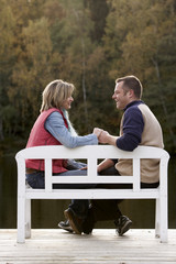 couple holding hands on a bench at a lake in autumn