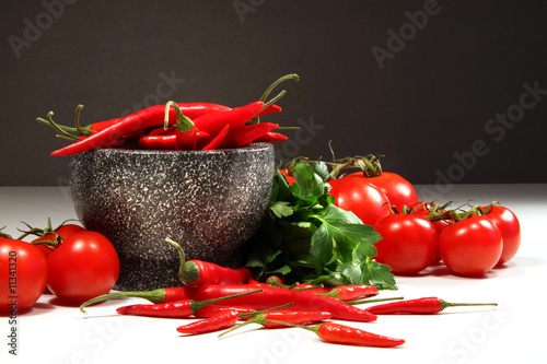 Red peppers and tomatoes with granite bowl on dark
