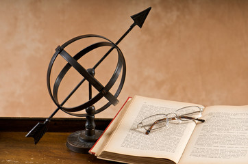Old armillary with book and eyeglasses.