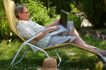 Senior man using laptop outdoor