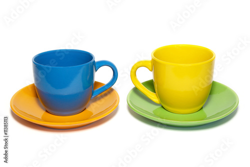 Colored teacups and saucers isolated on white.