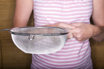 Close up of woman holding colander