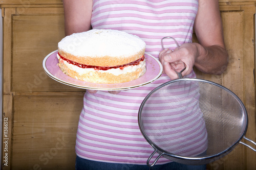 Close up of woman holding cake and colander