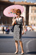 Lovely woman with pink sunshade in Rome town