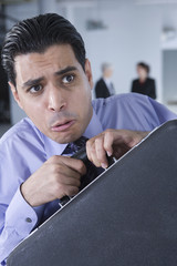 Fearful businessman holding his briefcase
