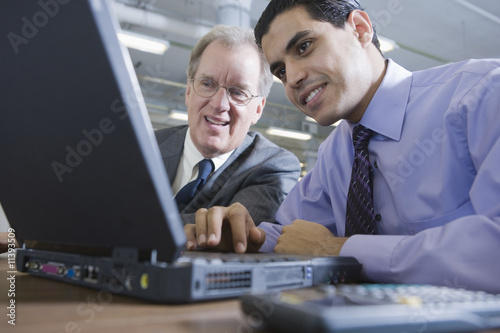 Two businessman with laptop and phone