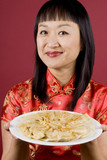 Chinese Woman Holding a Plate Full of Dumplings poster