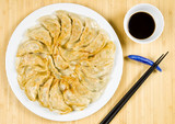 Plate Full of Fried Chinese Dumplings on Bamboo Place Mat poster